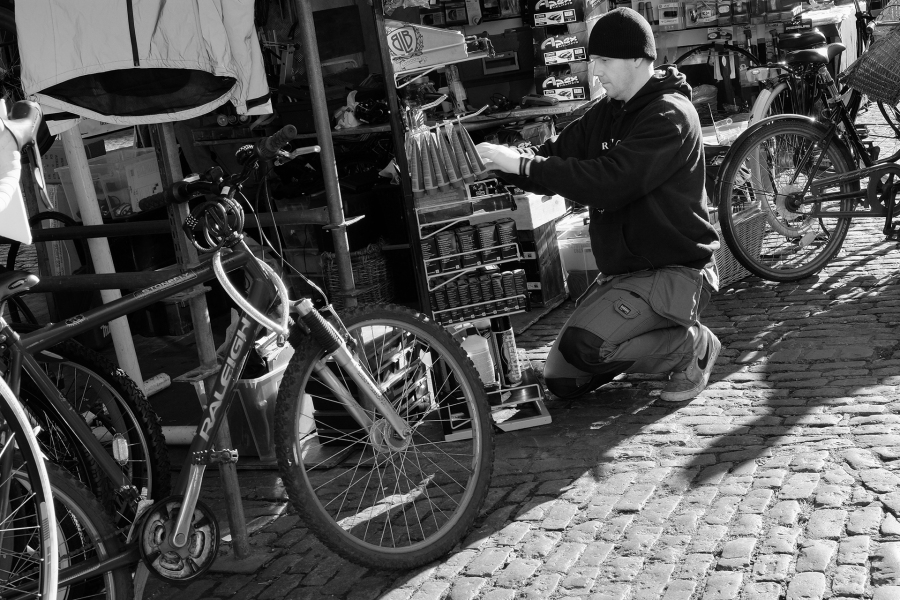 Guy working on a market stall. Bikes were everywhere in Cambridge. X-T1; XF18-55 @ 55; 1/90 sec; f/11; ISO 400