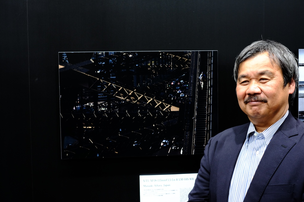 Masaaki Aihara standing next to one of his prints on the CP+ stage
