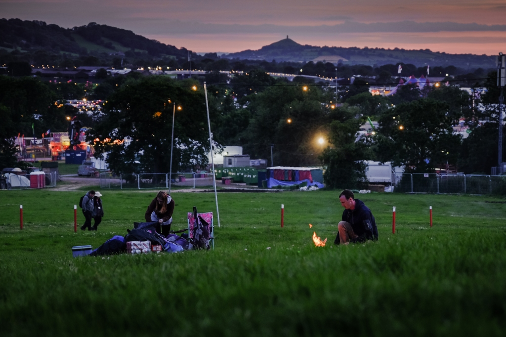 Glastonbury Festival, Somerset, UK. 23 June 2015. On the night before the Glastonbury Festival opens to the public festival participants build a small fire to keep warm. © Tom Corban