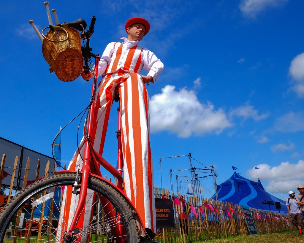 Glastonbury Festival, Somerset, UK. 27 June 2015. Rain, what rain. Stilt wearing bicycle riders prepare to entertain the crowds in the Theatre & Circus area as Saturday turns into a scorcher. © Tom Corban