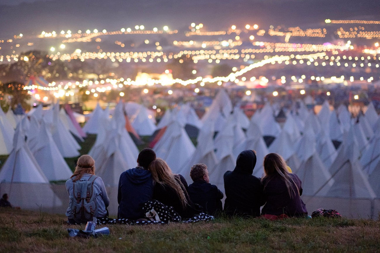 Revelers watch the sun rise from the Stone Circle as Glastonbury Festival comes to an end at Worthy Farm, Somerset. June 29 2015.