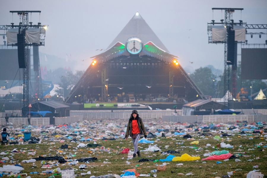 Revelers begin to head home through a sea of rubbish near the Pyramid Stage as Glastonbury Festival comes to an end at Worthy Farm, Somerset. June 29 2015.