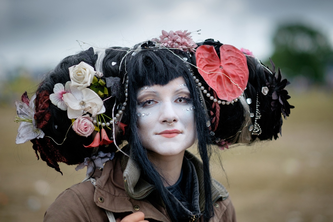 A dressed up woman poses for a photograph as revelers start to make their way home as Glastonbury Festival comes to an end at Worthy Farm, Somerset. June 29 2015.