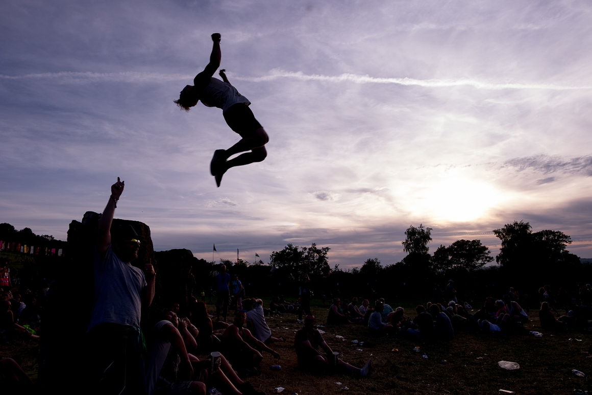 Edvinas Meilutis performs various flips as revelers relax at the Stone Circle as the sun sets at Glastonbury Festival 2015, on Worthy Farm, Somerset. June 25 2015.