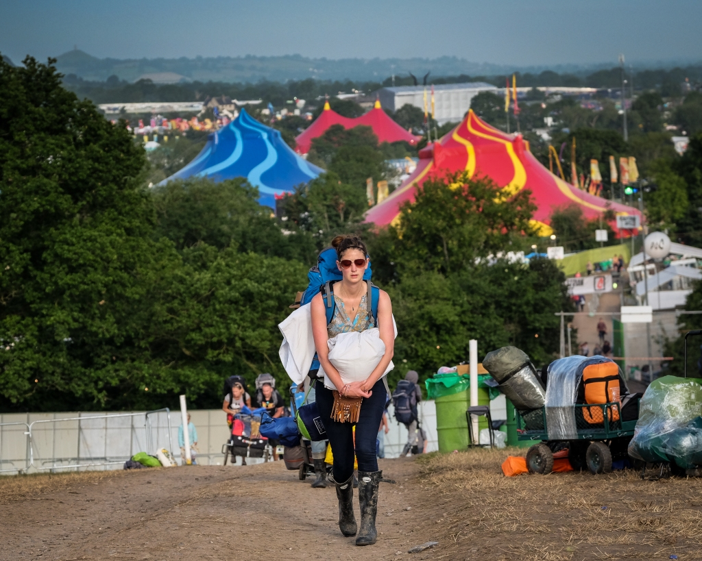 Glastonbury Festival, Somerset, UK. 29 June 2015. On the morning after the Festival ends a weary reveller makes her way up the hill and out of the Festival Site. © Tom Corban