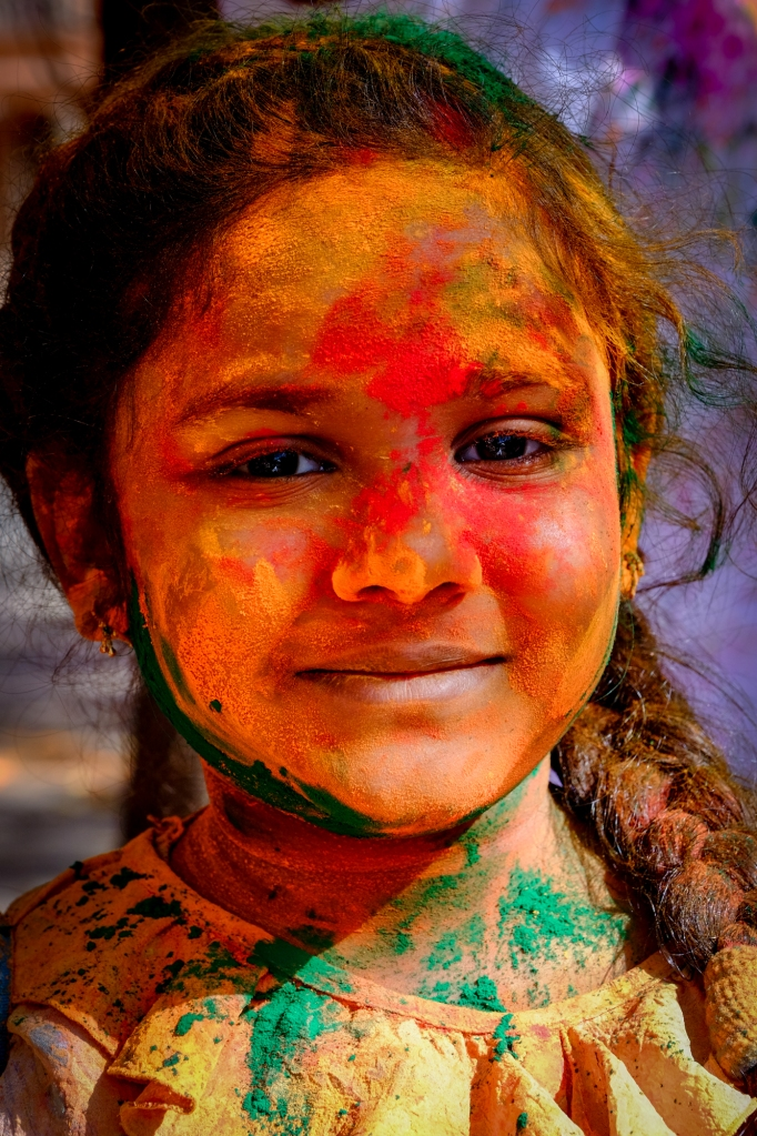 A child covered in coloured dye during Holi Festival, Jaipuri, Rajastan, India. Holi is a Hindu festival celebrating the beginning of spring. Bonfires are lit the night before Holi and offerings made to ensure a good harvest. The main Holi festival takes place the following day when people throw coloured dye on each other. It is often celebrated privately within family groups but in the streets anyone is fair game. Holi provides an opportunity to disregard social norms and young men have been known to act disrespectfully as the day goes on. Advice is given for single women to avoid going out alone and for tourists to be off the streets by early afternoon.
