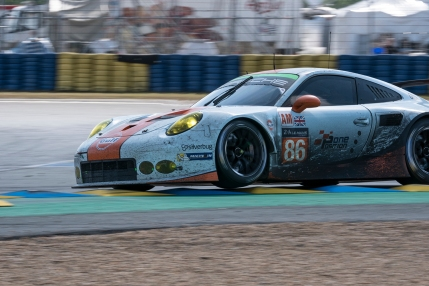 The no86 Gulf Racing Porsche taking the last corner at speed at Le Mans.