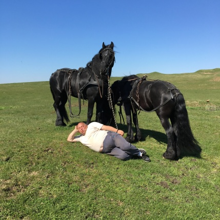 Animal wrangler resting between takes with his horses